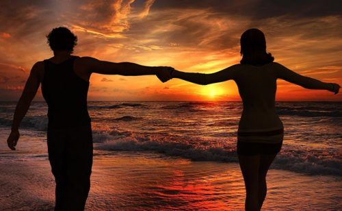 Par på stranden ved solnedgang